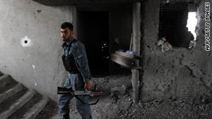 An Afghan security officer stands at the site where insurgents launched attacks Wednesday.