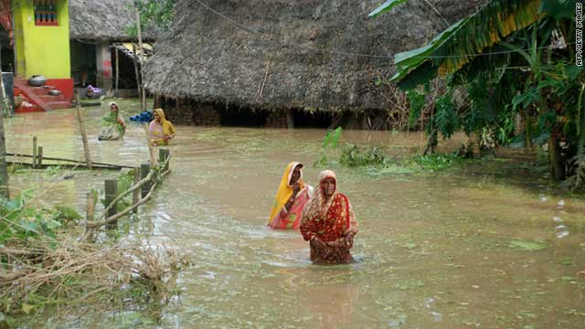 Indian villagers wade though flood waters near Mahanga Panchayat in Orissa's Cuttack district on September 13, 2011.