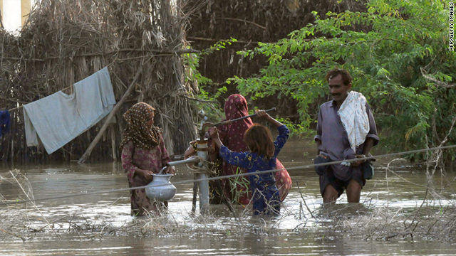 People gather around a water pump in the flooded area on the outskirts of Badin, Pakistan, on Sunday.
