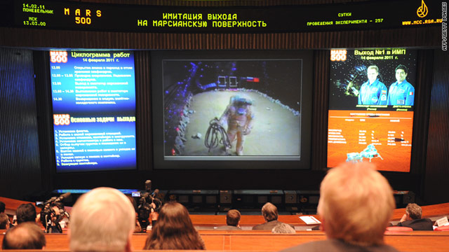 Journalists watch a mock walk on Mars of volunteers of the Mars500 experiment outside Moscow on Monday.