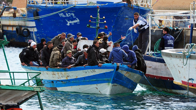 Immigrants in a boat are helped as they arrive in Lampedusa harbor off the southern Italian island on March 30, 2011.