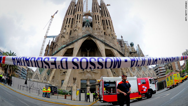 Firemen stand in front of the Sagrada Familia church on Tuesday in Barcelona after a fire broke out inside the church.