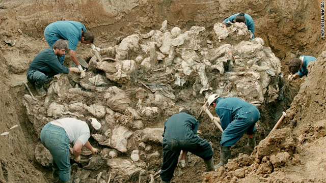 A photo dated July 24, 1996, shows International war crimes tribunal investigators examine a mass grave in Srebrenica.