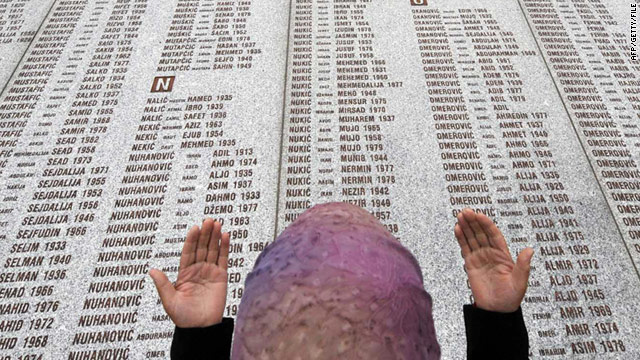 A woman prays at the memorial wall with the names of the victims at the Potocari Memorial Center near Srebrenica in 1998.