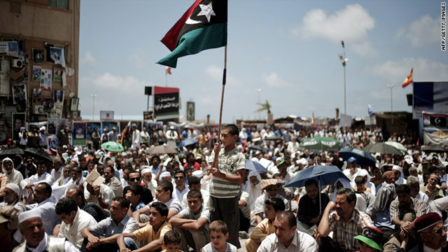 A boy holds up the former Libyan monarchy flag-- the sign of the Libyan revolution-- in the rebel stronghold of Benghazi, Libya.