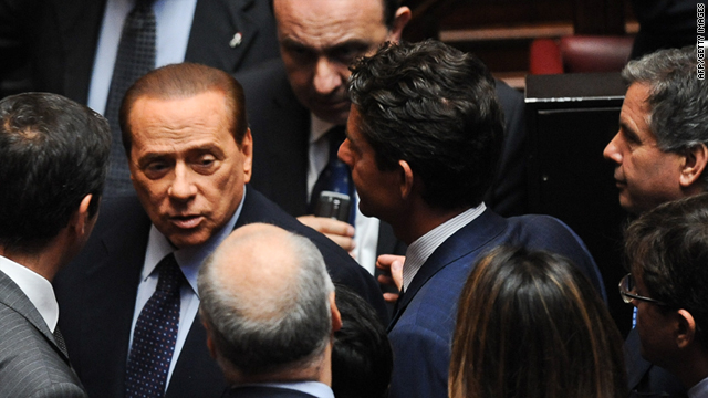 Silvio Berlusconi speaks with members of his party after they won a confidence vote on a bill at Italy's Chamber of Deputies