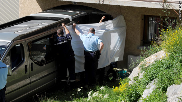 Officials hold a white sheet up to block the view as bodies are loaded into a mortuary van Sunday.