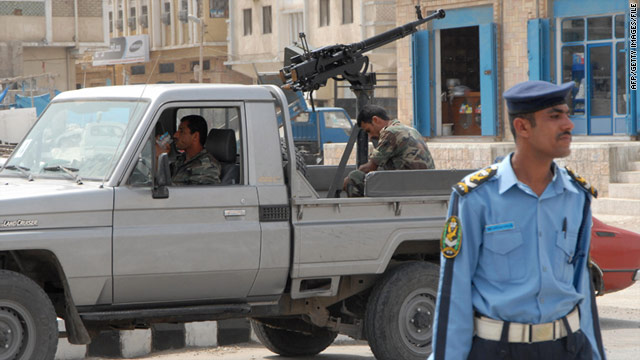 Police stand guard in the Yemeni city of Mukalla, where 63 prisoners escaped last week.