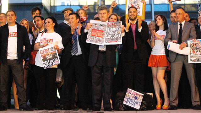 News of the World staffers hold up copies of the final edition of the paper outside of their London newsroom Saturday night.