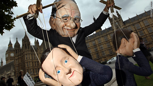 A demonstrator in a Rupert Murdoch mask controls a puppet of PM David Cameron in a protest outside the Houses of Parliament.