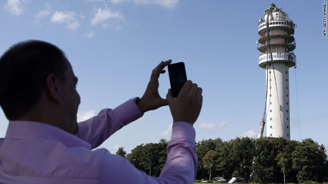 A man takes a photo of the partially destroyed TV tower in Hoogersmilde.
