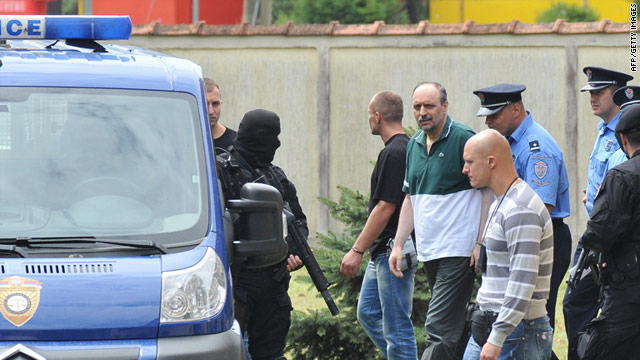 Police secure the area while Goran Hadzic (center) is taken to see his ailing mother ahead of his transfer to the Netherlands.