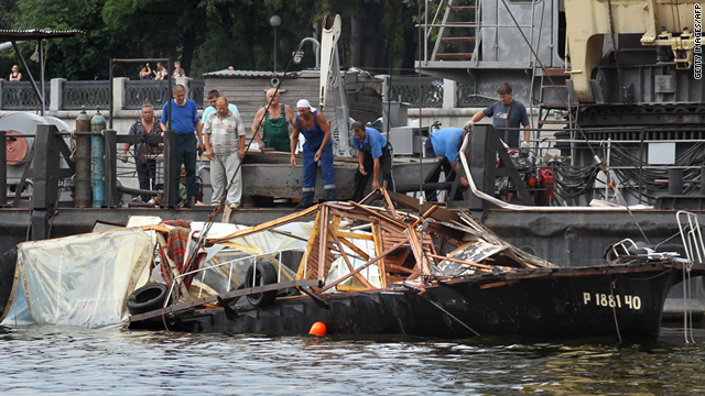 Rescue workers examine the wreckage of the sunken boat in the Moskva river in Moscow, Russia, on July 31.