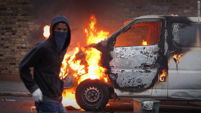 A masked youth walks past a burning vehicle in Hackney, London on August 8.