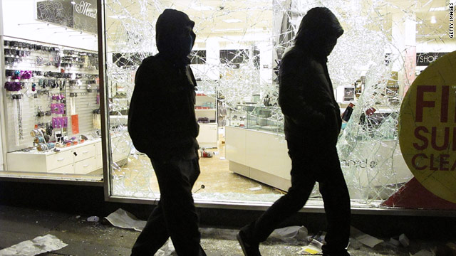 Hooded youths walk past a looted department store in Clapham Junction, London, on August 8.