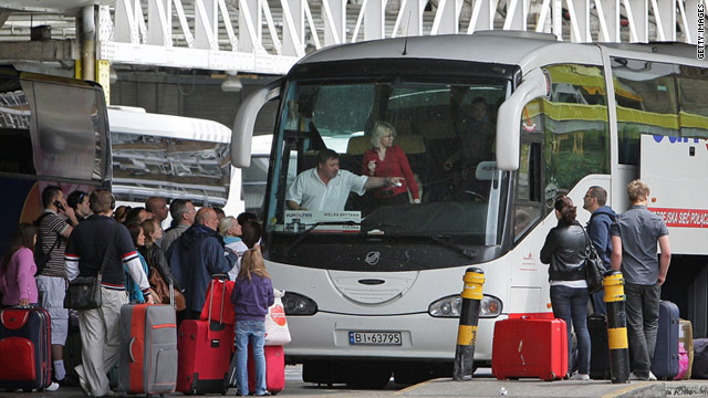 Passengers board a bus leaving for Poland from London