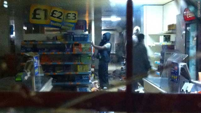 Youths try to set fire to shelves of goods inside a retail store in Tottenham, north London, on August 6, 2011.