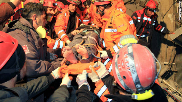 Rescuers carry a survivor from a collapsed building after an earthquake struck eastern Turkey Wednesday night.