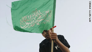 A Palestinian boy waves the green flag of Hamas, which  controls Gaza.