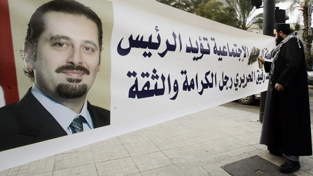 A Sunni Muslim cleric from the pro-Hezbollah Islamic Labour Front sprays his family's name on a banner supporting Lebanon's caretaker prime minister Saad Hariri (portrait) in Sidon on January 18.