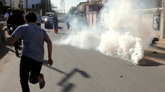 Protesters run for cover after police fired tear gas canisters to disperse them in the village of Diraz in northwest Bahrain.