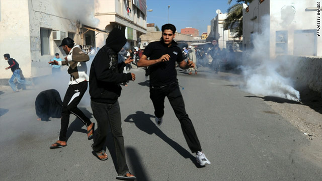 Bahraini protestors run for cover as police fire tear gas in the village of Diraz, northwest of Bahrain, on February 14.