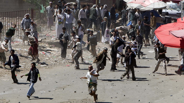 Yemeni regime loyalists throw stones towards anti-government protesters during clashes in central Sanaa on Thursday.