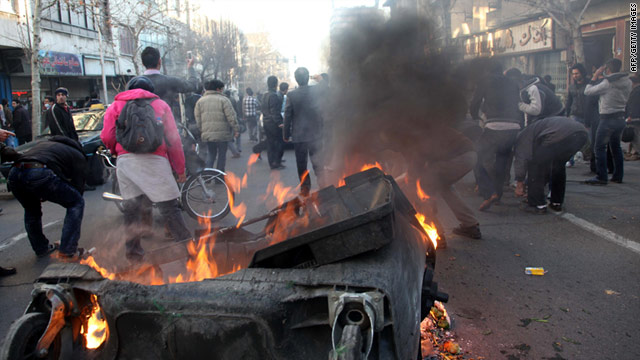 Garbage containers are set on fire as Iranian protesters stage an anti-government demonstration on February 14, 2011.