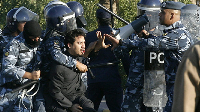 Kuwaiti riot policemen detain a man during clashes Friday between police and stateless Arab protesters in Jahra City.