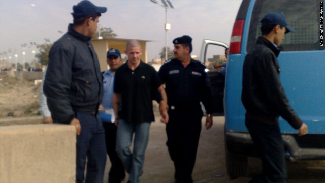Daniel Fitzsimons, center, is escorted by Iraqi police in Baghdad after a court appearance in January.