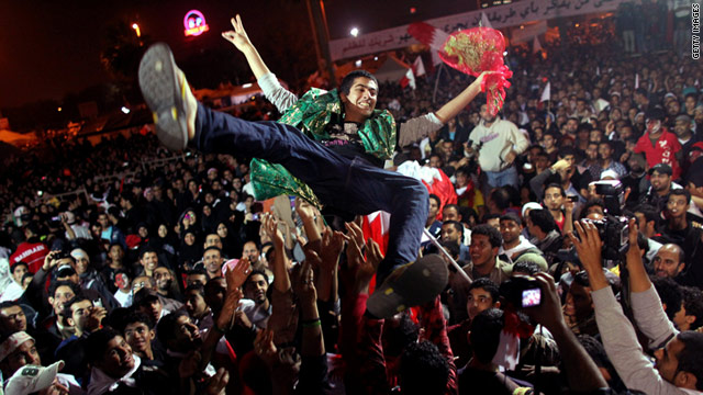 Bahraini protesters hoist a released political prisoner in the air at Pearl roundabout, Manama, on February 22, 2011.
