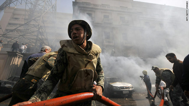 Soldiers help extinguish a fire at a building adjacent to the interior ministry set by former police officers in downtown Cairo.