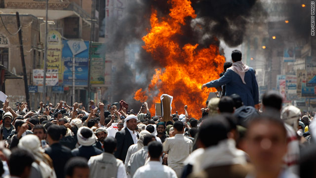 Protesters gather around a burning vehicle belonging to government supporters during a protest in Sanaa on Tuesday.