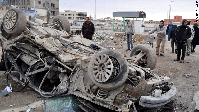 Iraqis inspect the site of a bombing that rocked the western city of Ramadi in this file photo from February 4, 2011.