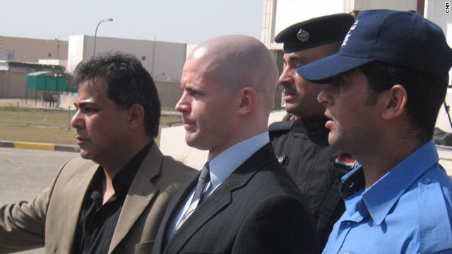 Iraqi police escort British contractor Daniel Fitzsimons out of court in Baghdad, where he was sentenced to life in prison Monday.
