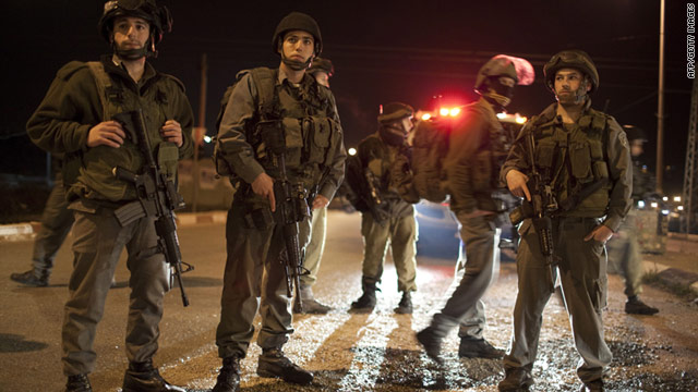 Israeli soldiers block the road in the Hawara checkpoint near the West Bank city of Nablus on Saturday, March 12.