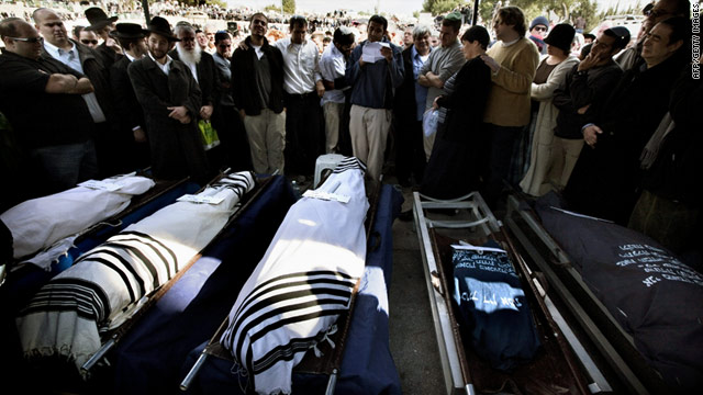 Relatives and friends mourn over the bodies of five murdered Israeli settlers on Sunday in Jerusalem's cemetery.