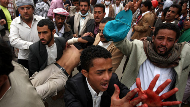Yemeni anti-government protesters carry away a wounded demonstrator in Sanaa on Friday, March 18.