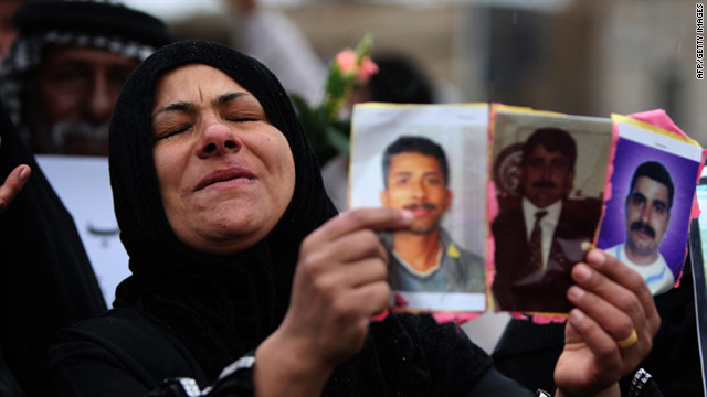 An Iraqi woman holds pictures of relatives held in jails during a demonstration calling for their release in Baghdad on Friday.