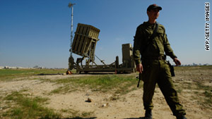 "An Israeli soldier stands next to a launcher, part of the countyr's ""Iron Dome"" defense system."