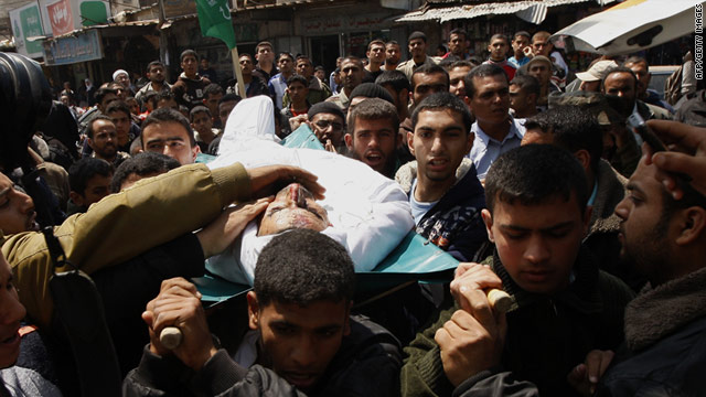 Young Palestinian men bear the body of Hamas commander Taysir Abu Snima, who was killed Saturday in an Israeli airstrike.