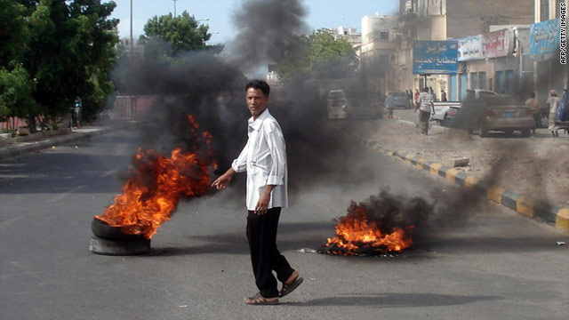 A man walks past burning tires in Aden on Wednesday, after the Yemeni army shot dead two anti-regime protesters.