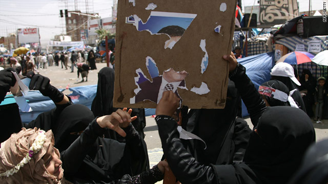 Yemeni anti-government protesters tear up a poster of president Ali Abdullah Saleh in Sanaa on Sunday.