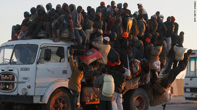 Foreign workers pile onto the back of a truck with their belongings as they leave the besieged city of Misrata April 18, 2011.