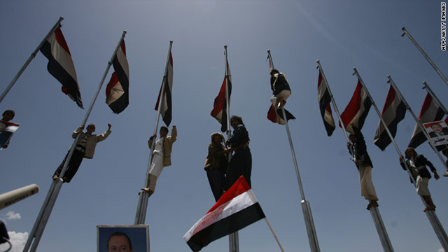 Supporters of President Ali Abdullah Saleh climb on flag poles during a rally held in the capital Sanaa on April 15, 2011.