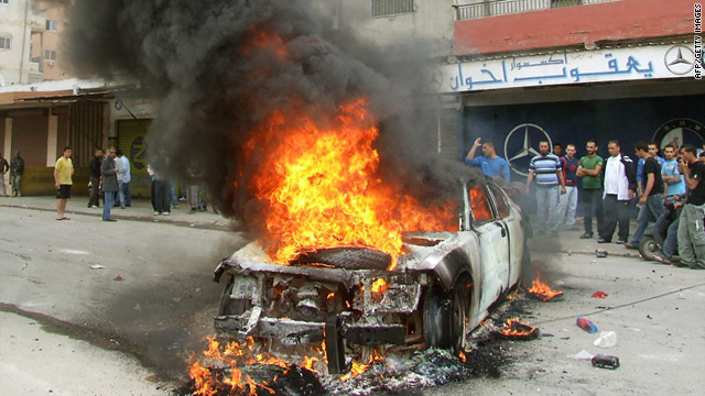 Lebanese men gather around a burning police car during a protest in the southern port city of Tyre on Thursday.