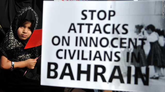 An Indian child stands next to a placard during a protest against the political turmoil in Bahrain in Mumbai on March 25, 2011.