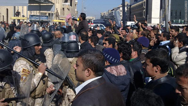 Demonstrators face security personnel in Mosul on Tuesday. They protested the U.S. troop presence in Iraq and other issues.