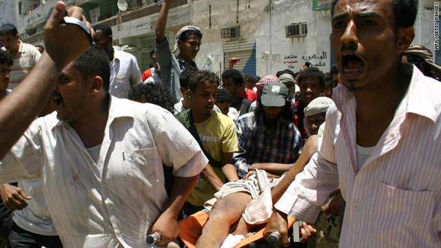 Yemeni men shout as they carry away an injured protester in the southern port city of Aden on Saturday, April 30.