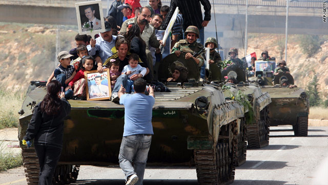 Army vehicles retreat from Daraa on Friday -- human rights organizations say dozens of people were arrested in the city.